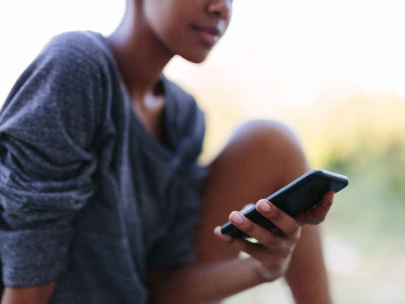 Blurred Image of woman viewing a smartphone