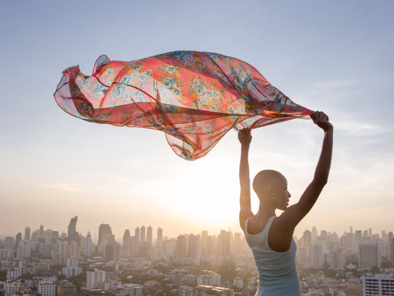 Woman viewing a sunset and waving a scarf with a Cityscape in the Background